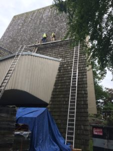 The roofing crew brave the heat as they begin removal of the old cedar shakes.